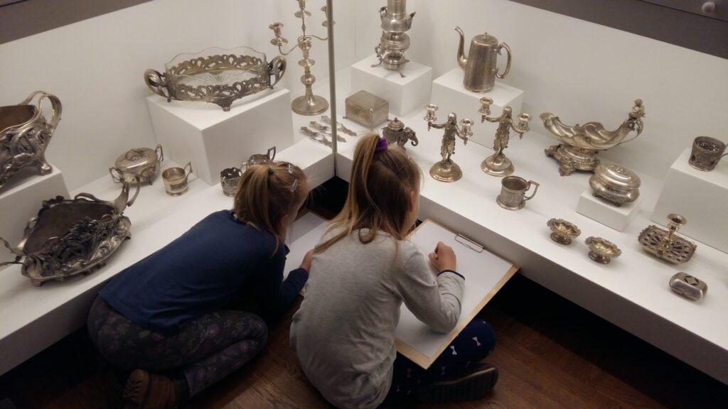 Dwie, kilkuletnie dziewczynki przyglądają się srebrnym przedmiotom w szklanej gablocie. Każda ma białą kartkę i ołówek. Przygotowują się do rysowania.