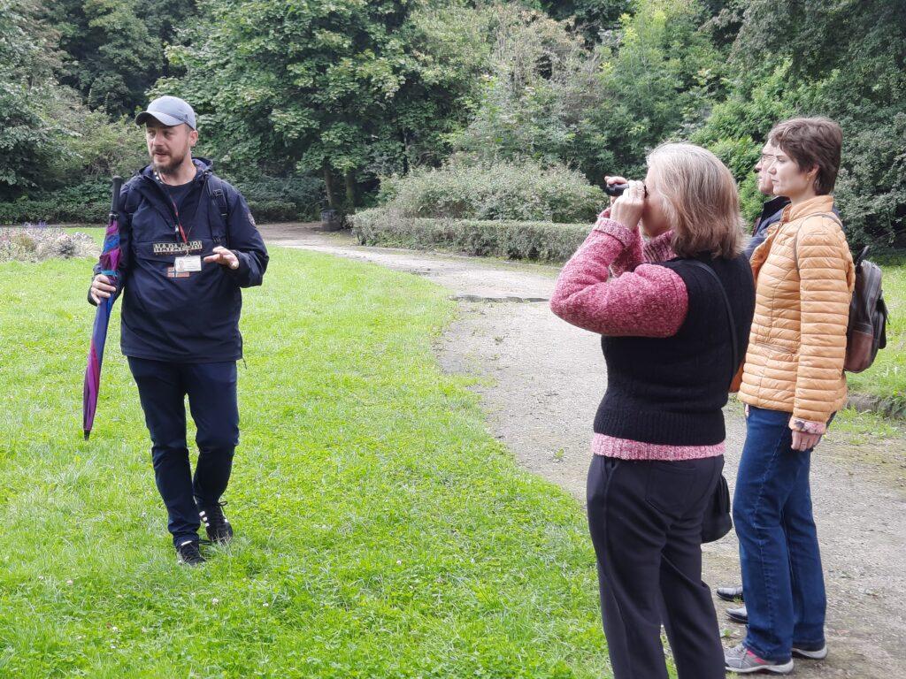 Zdjęcie. Park. Grupa kilku osób z przewodnikiem. Na pierwszym planie kobieta patrzy na coś przez monokular.