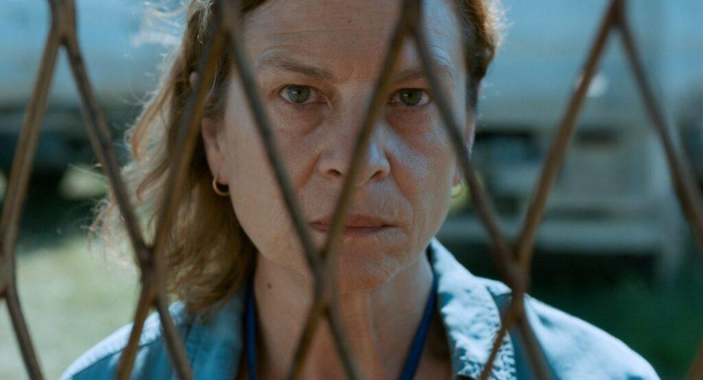 Zdjęcie przedstawia starszą kobietę, bohaterkę filmu smutno spoglądającą zza krat płotu.