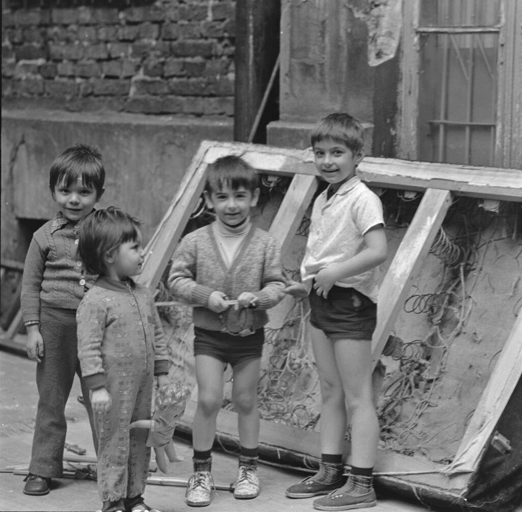 Podwórko. Przy ścianie kamienicy. Grupka dzieci bawi się obok opartego o ścianę zniszczonego, tapicerowanego łóżka. Widać drewnianą ramę i duże sprężyny.