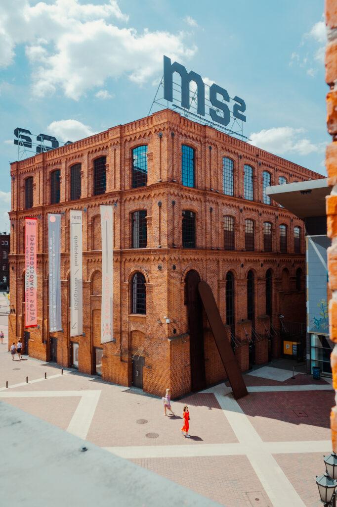 Widok na siedzibę Muzeum Sztuki w Łodzi, ms2. Budynek ceglasty o czterech kondygnacjach i łukiem zakończonych oknach. Na dachu budynku wielkie czarne litery ms2.