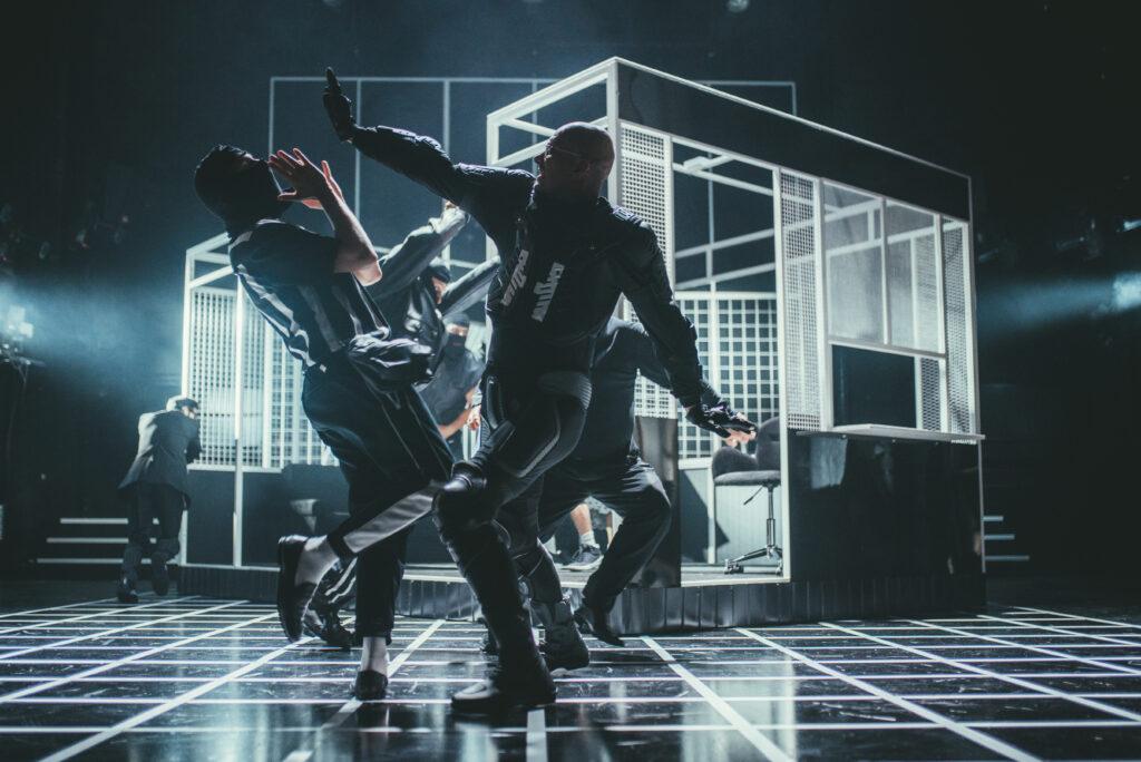 W półmroku walczy dwóch mężczyzn ubranych na czarno. W tle, za nimi, stoi metalowa konstrukcja przypominająca kiosk Ruchu.