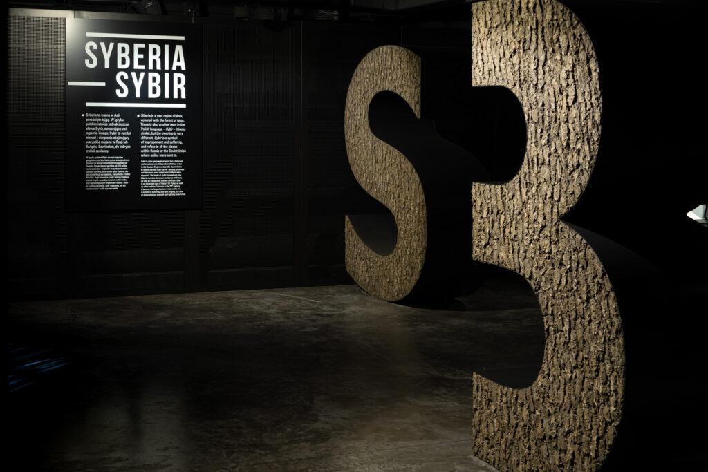 Przestrzeń wystawy. Duże kamienne litery S i B, w tle plansza z informacjami i hasłem Syberia - Sybir.