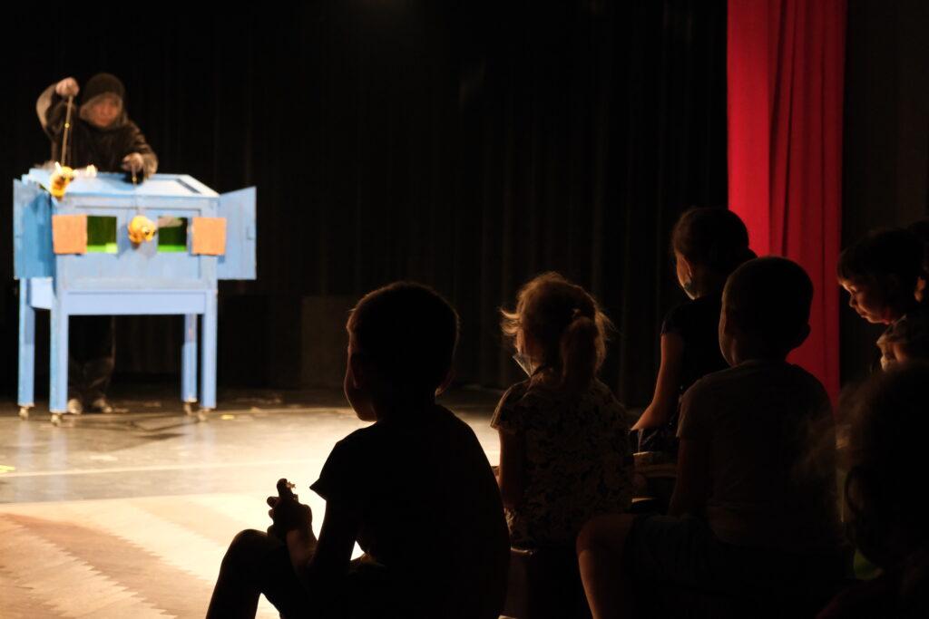 Grupa dzieci patrzy na akcje sceniczną.
