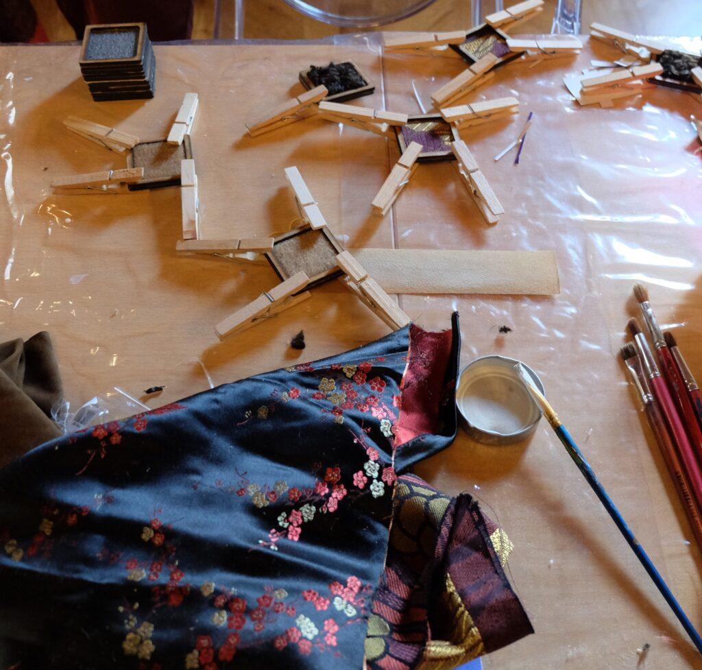 Widok z góry na stół. Leżą na nim: tkaniny, pędzelki oraz kilka kwadratowych, drewnianych płytek. W narożnikach zaczepione mają klamerki.