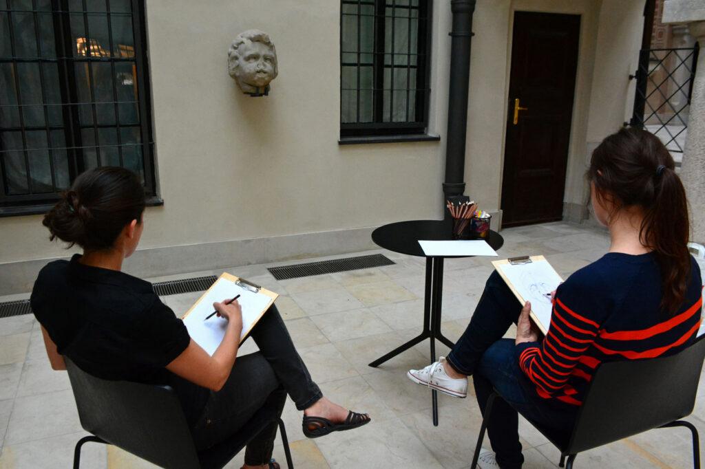 Dwie kobiety siedzą na krzesłach na podwórzu. Przyglądają się maszkaronowi na ścianie kamienicy. Szkicują.