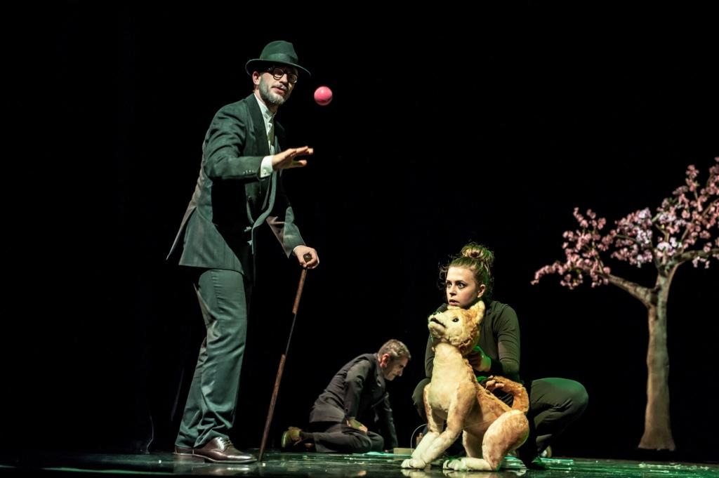 Zdjęcie spektaklu. Po prawej stronie widzimy eleganckiego pana w ciemnym garniturze, kapeluszu, z laską, który podrzucił w górę czerwoną piłeczkę. Po lewej stronie pies o blond sierści szykuje się do skoku po piłkę. Piesek to lalka teatralna animowana przez ubraną w czarny dres aktorkę. Tło jest czarne. Z tyłu widzimy siedzącego na ziemi człowieka, a po lewej kwitnące drzewo.