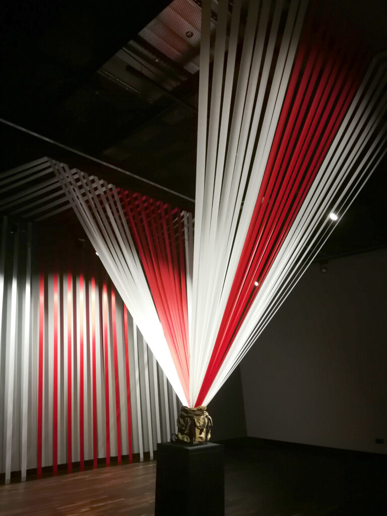 Na zdjęciu jeden z eksponatów wystawy ŻYWIE BIEŁARUŚ! NIECH ŻYJE BIAŁORUŚ! Plecka z którego wychodzą biało-czerwone wstążki.