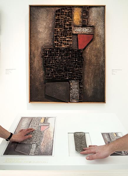 Zdjęcie ukazujące dwie ręce dotykające tyflografikę z pracą Zdzisława Beksińskiego.