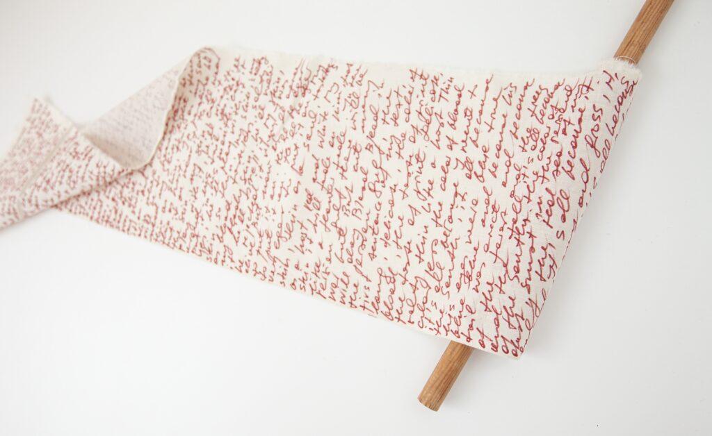 Rolka białej bawełny, na której gęsto zapisano tekst czerwonym flamastrem.