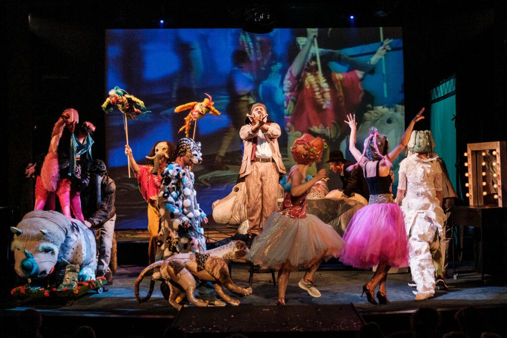 Na scenie biegają zwierzęta. Reżyser Pan Soczewka w centralnej części sceny próbuje zarządzić rozbieganymi zwierzętami.