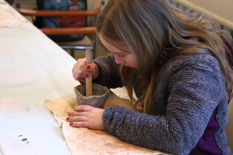 Zdjęcie. Dziewczynka w jasnobrązowych włosach i fioletowej bluzie drewnianą łopatką ozdabia szare naczynie z gliny. Stół przykryty białą ceratą.