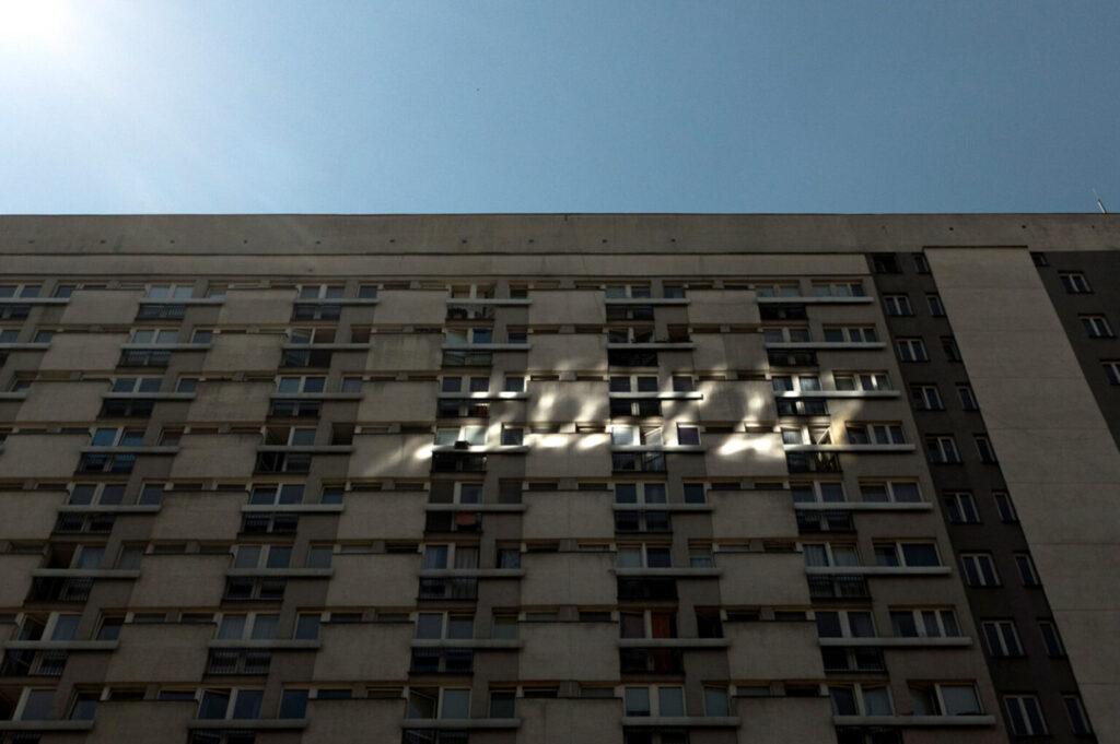 Zdjęcie. Duży blok, spowity cieniem. Na fasadzie plama światła odbitego od szyby lub karoserii samochodu.
