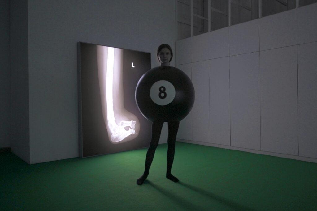 Zdjęcie: widok wystawy, przygaszone światło, jasnozielona wykładzina; pośrodku stoi kobieta w czarnych rajtuzach, tułów ukryty w ogromnej, czarnej bilardowej kuli z numerem 8; w tle lightbox, na nim rentgen kości kończyny.