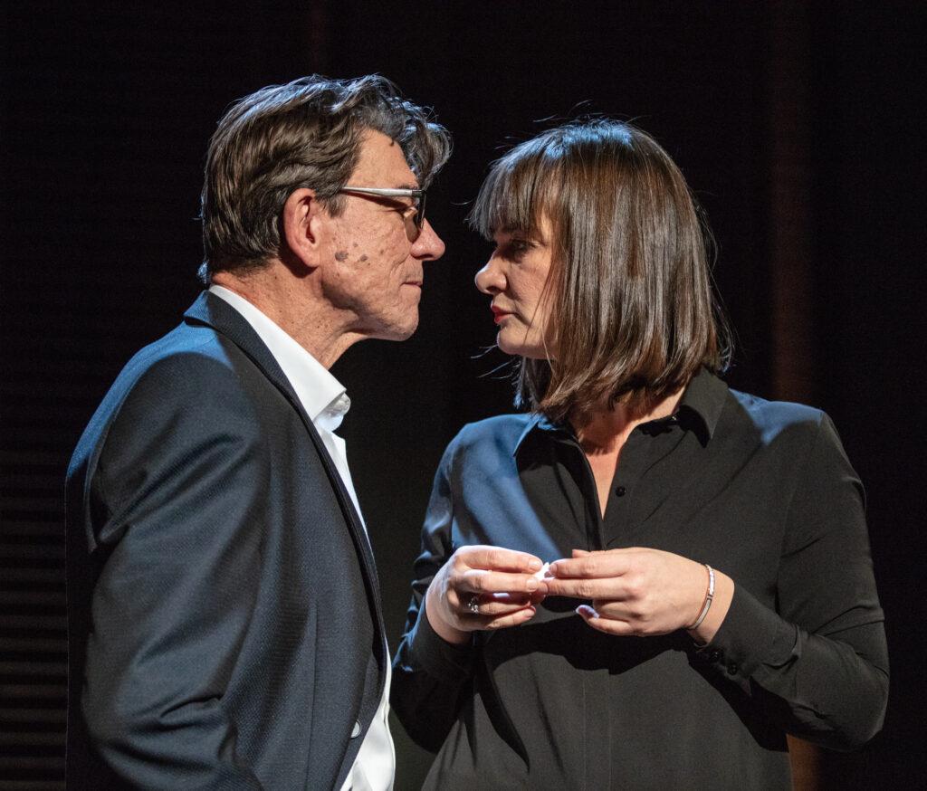 Ujęcie ze spektaklu. Kobieta i mężczyzna stoją naprzeciwko siebie i patrzą sobie w oczy.