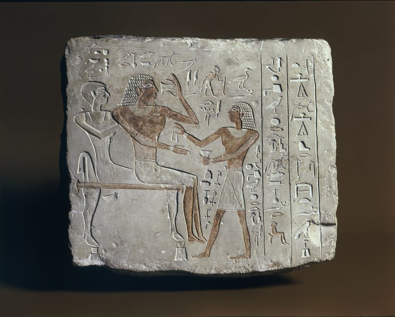 Kamienna stela. Po lewej Nefer i jego żona siedzą na ławie. Z prawej podchodzi do nich syn. Powyżej i pomiędzy postaciami hieroglify.