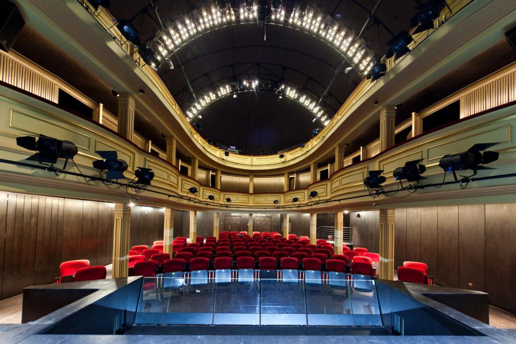 Widok na salę widowiskową Teatru Starego z poziom sceny; na pierwszym planie puste rzędy krzeseł widowni, w tle loże i balkony.