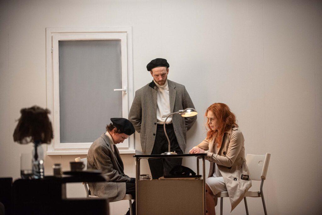 Dwie smutne kobiety w średnim wieku siedzą naprzeciwko siebie przy biurku. Stoi na nim zapalona lampka. Z tyłu stoi mężczyzna, który opiera się o białą ścianę i patrzy w podłogę. Obok niego jest zamknięte i zasłonięte okno.