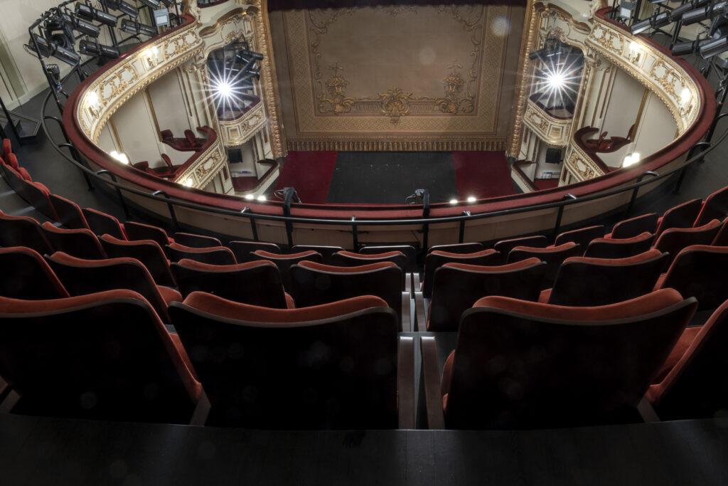 Zdjęcie przedstawia dużą scenę i widownię Teatru Horzycy. Zrobiono je z balkonu na drugim piętrze. Na pierwszym planie rzędy czerwonych foteli. W dole pusta scena z opuszczoną kurtyną ozdobioną złotymi, roślinnymi wzorami. Po obu stronach sceny reflektory.