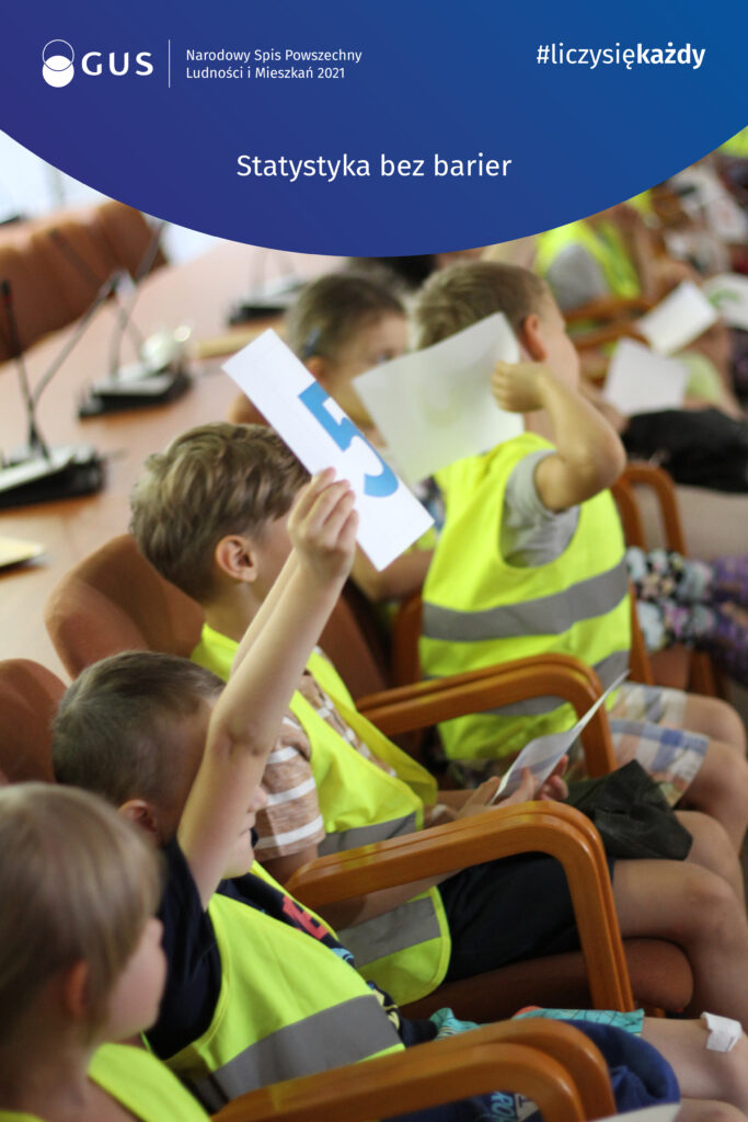 """Na górze napis ,,statystyka bez barier"""" wraz z hasztagiem liczy się każdy oraz logiem Głównego Urzędu Statystycznego. Poniżej zdjęcie grupy dzieci siedzących na krzesłach. Niektóre z nich trzymają kartki z napisanymi na nich cyframi."""