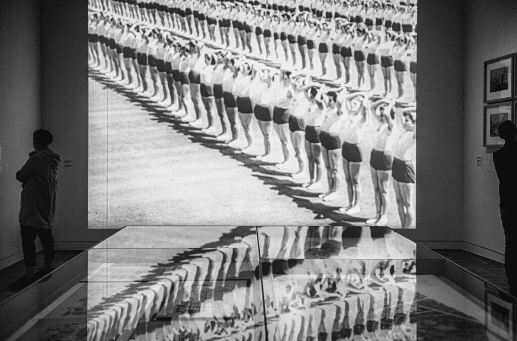 Czarno-białe zdjęcie: widok wystawy; na ścianie projekcja z rzędami gimnastyczek; ten sam obraz odbija się w szklanej gablocie.