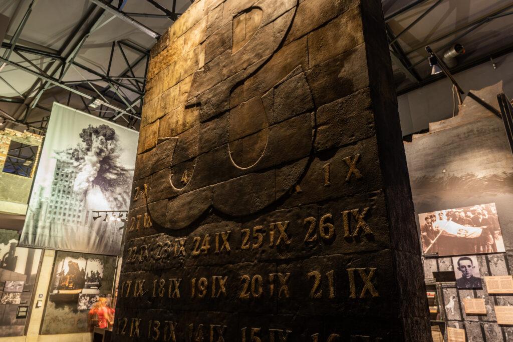 Zdjęcie fragmentu ekspozycji Muzeum Powstania Warszawskiego. Na środku stalowy monument z wypukłym znakiem Polski Walczącej i kalendarium Powstania. Fotograf Robert Danieluk.
