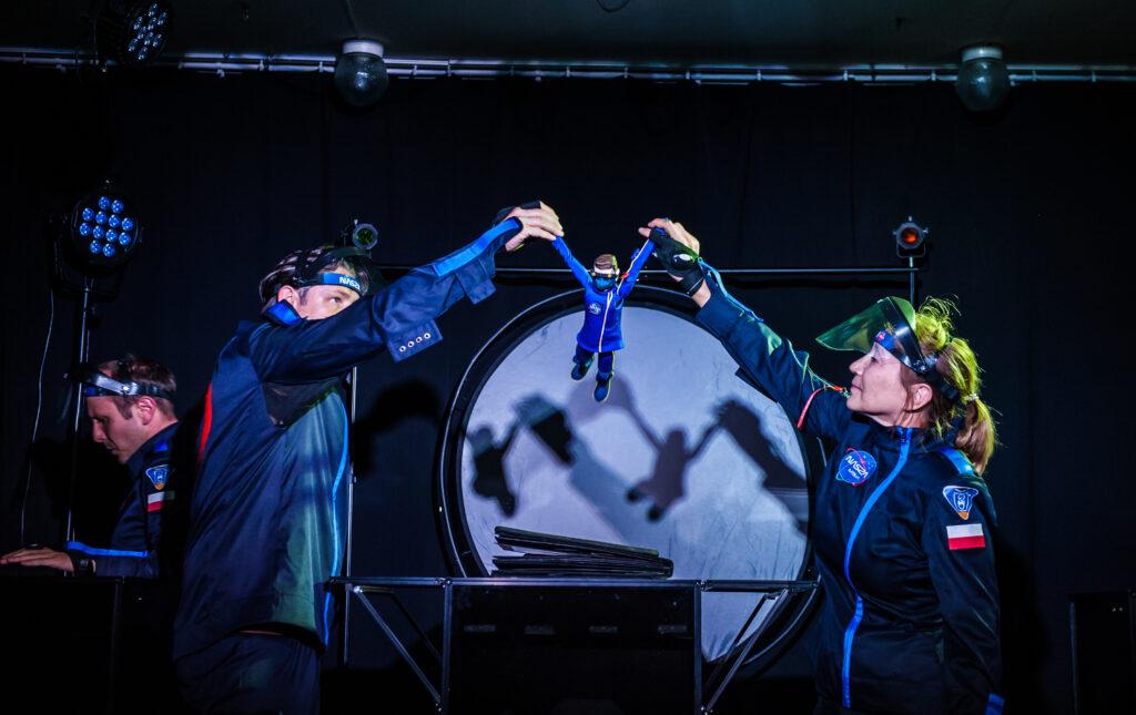 Dwóch aktorów ubranych w stroje pracowników stacji kosmicznej trzyma za ręcę i podnosi do góry małą lalkę - bohatera spektaklu.
