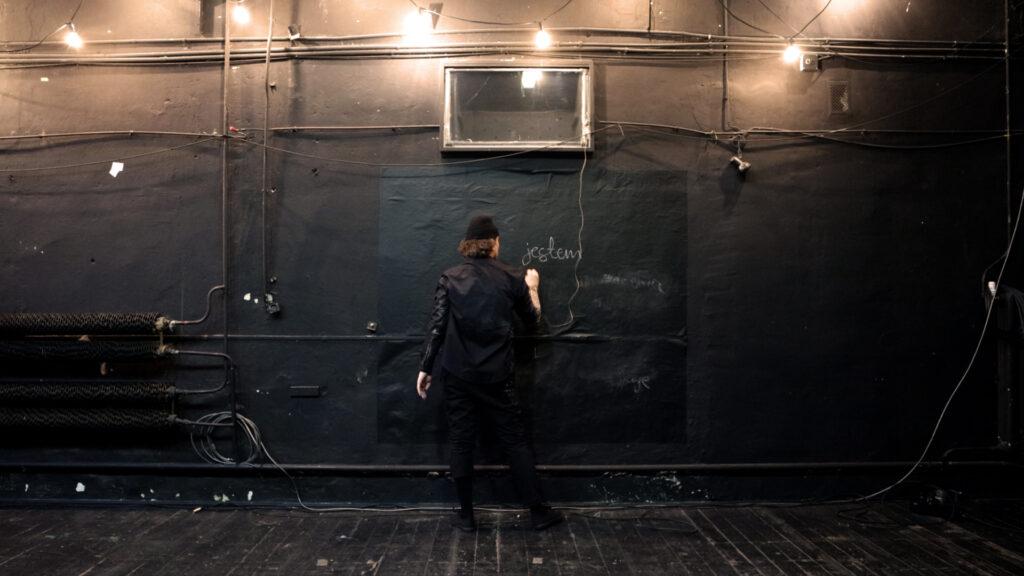 """Zdjęcie: ciemne wnętrze; podłoga, ściany, oraz elementy instalacji technicznych pomalowane na czarno; na środku mężczyzna ubrany na czarno, w czapce, tyłem do nas, pisze na ścianie, powyżej napis kredą """"jestem""""."""