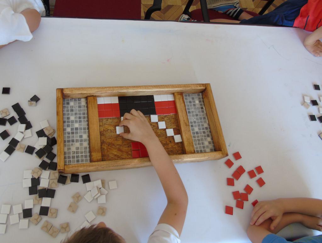Zdjęcie. Drewniany pojemnik do układania mozaiki z kolorowych kwadratów. Biały stół, na mim rozrzucone fragmenty mozaiki. Ręce dzieci układających mozaikę.