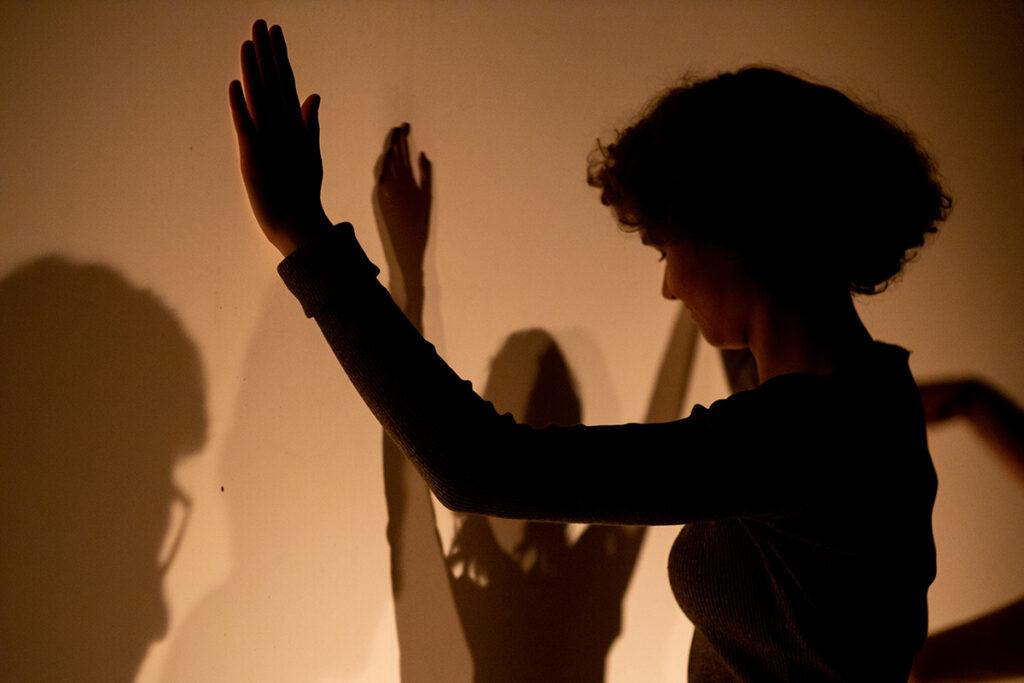 Kobieta stoi przodem do ściany, z rękami podniesionymi na wysokość głowy.