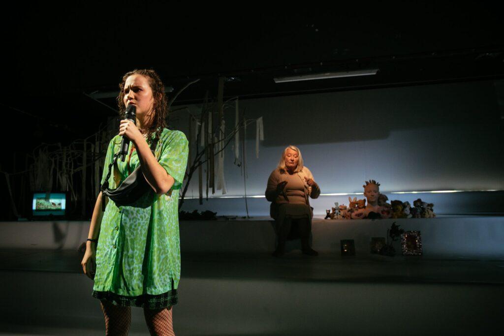 Na pierwszym planie stoi nastolatka, w zielonej koszulce i krótkiej spódniczce, przez ramię ma przewieszoną torbę typu