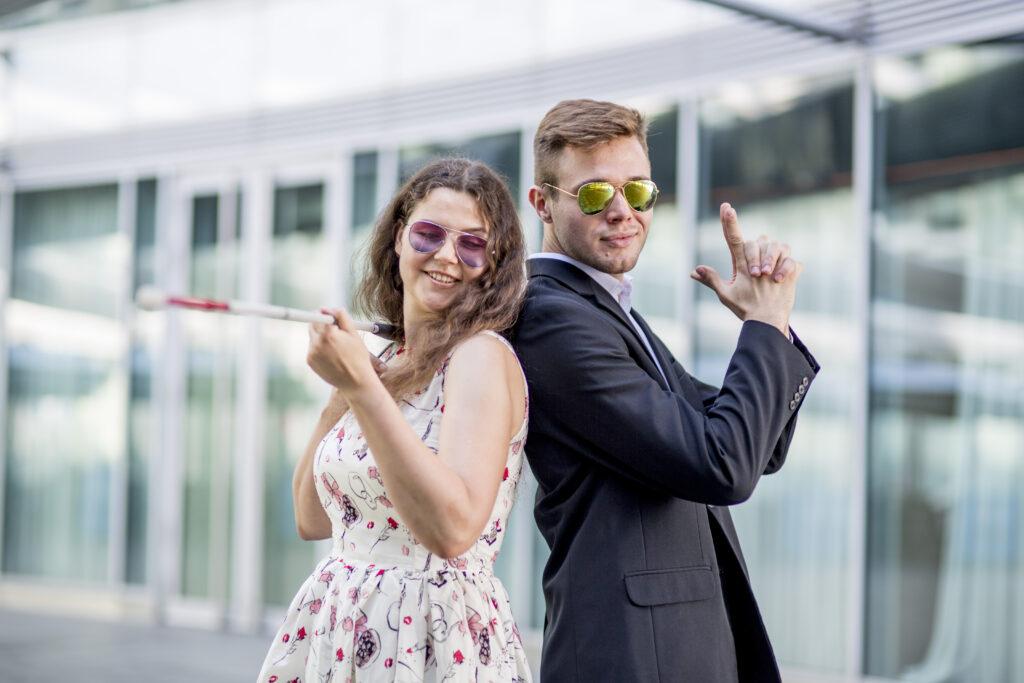 Zdjęcie przedstawia Monikę i Mikołaja, stojących razem, plecami do siebie, uśmiechniętych, patrzących w stronę oglądającego. Mają słoneczne okulary.