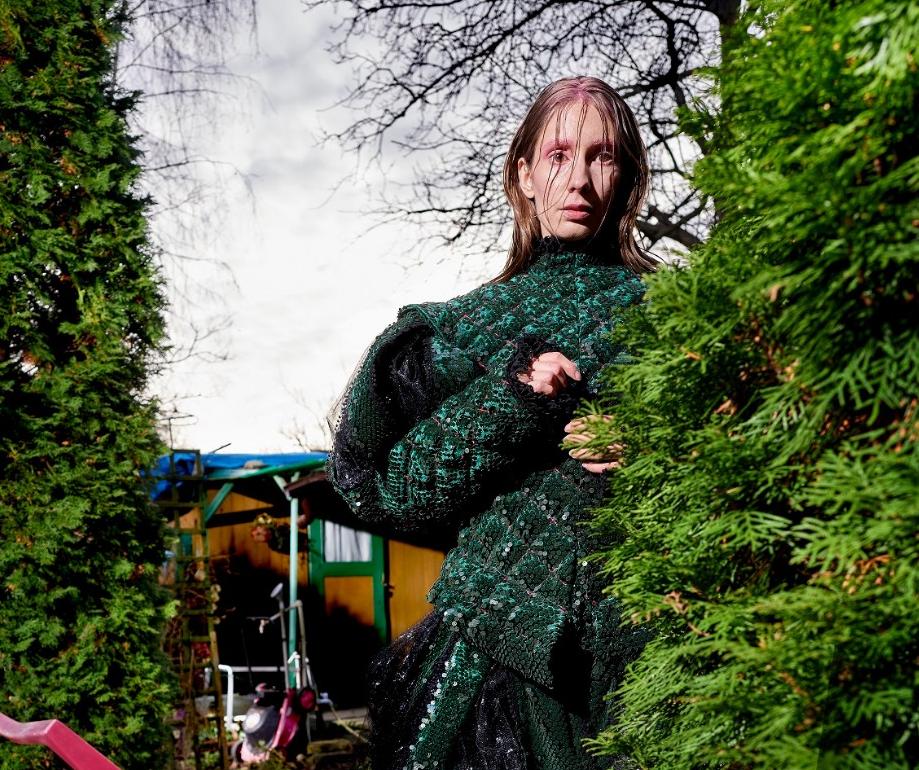 Dziewczyna w zielonej sukni z nieuczesanymi włosami stoi za zieloną choinką.