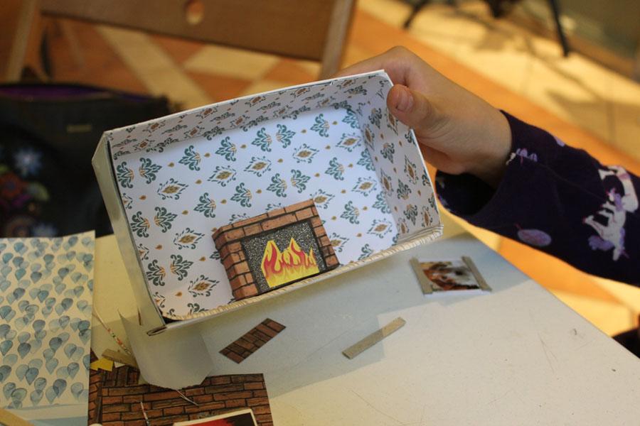 Diorama w wykonaniu uczestniczki warsztatów. Małe pudełeczko wyklejone w środku wzorzystym papierem, dodatkowo naklejone mniejsze pudełko imitujące kominek.