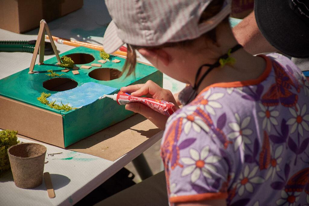 Słoneczny dzień. Dziecko przy stole warsztatowym ozdabia kartonowe, pomalowane na zielono pudełko.
